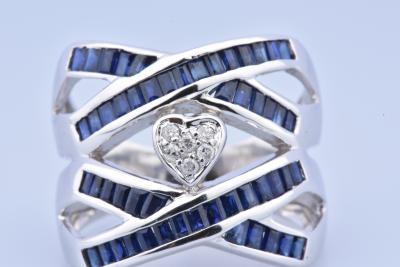 Beautiful ring in 18 carat white gold (750 thousandths), composed of crossed sapphires and a diamond heart.